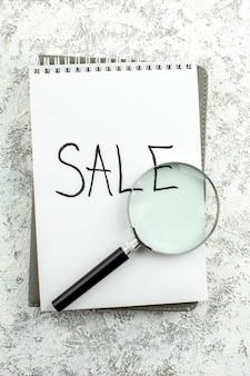 Vue de dessus vente concept publicitaire écrit sur le bloc-notes lupa sur table grise