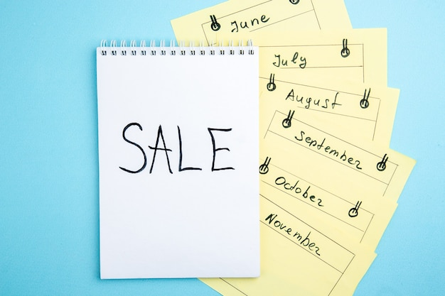Vue de dessus vente écrite sur des cartes de rappel mensuel du bloc-notes sur fond bleu