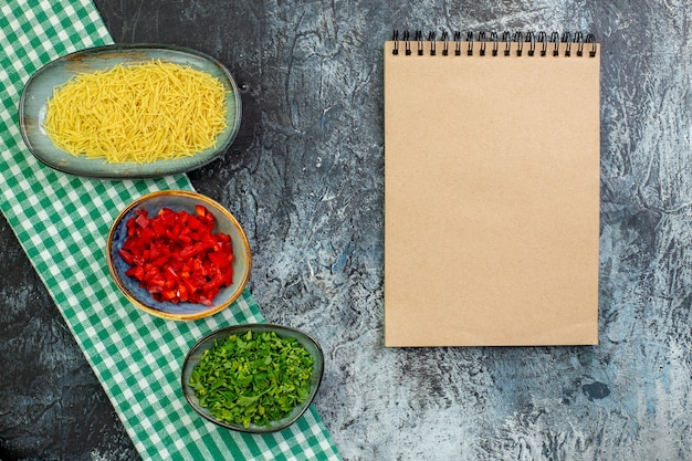 Vue de dessus des vermicelles crus avec des verts et du poivron tranché sur une table grise