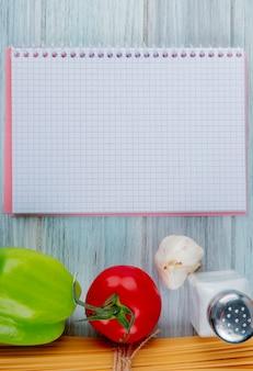 Vue de dessus des vermicelles macaroni à l'ail et au sel de tomate avec bloc-notes sur une surface en bois avec copie espace