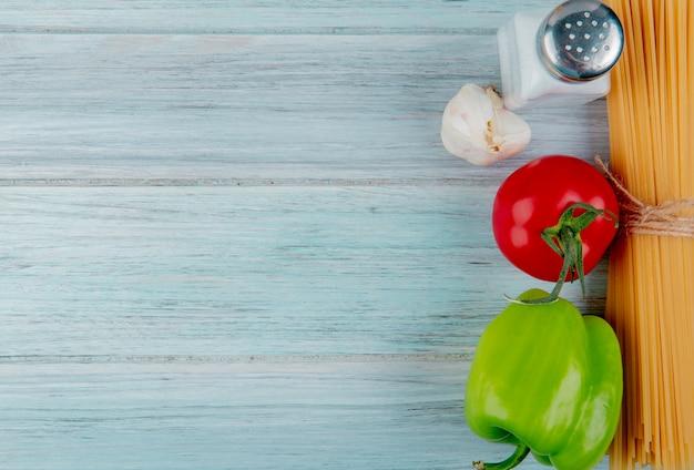 Vue de dessus des vermicelles macaroni à l'ail et au sel de tomate sur la surface en bois avec copie espace