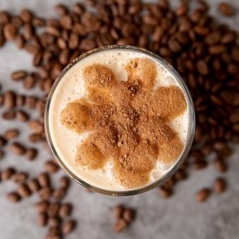 Vue de dessus verre de cappucino avec grains de café