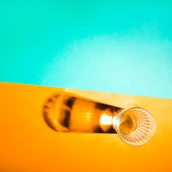 Une vue de dessus de verre avec une ombre lumineuse sur fond jaune et turquoise