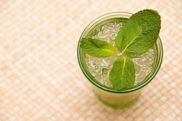 Vue de dessus d'un verre de thé glacé avec des feuilles de menthe sur la table
