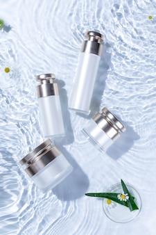 Vue de dessus verticale des bouteilles de soins de la peau sur une surface d'eau blanche