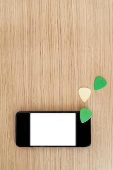Vue de dessus verticale de l'écran du smartphone avec un contenu vierge. étudier et apprendre le concept en ligne de leçons de guitare. explorez la musique et la technologie ensemble. médiators et espace de copie de téléphone à écran blanc.