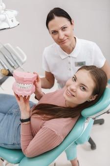 Vue de dessus verticale tourné d'une belle femme heureuse et son dentiste souriant à la caméra après un traitement dentaire