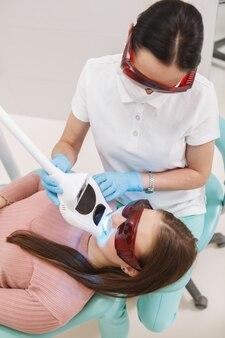 Vue de dessus verticale tourné d'un dentiste professionnel faisant le blanchiment des dents pour une patiente