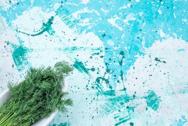 Vue de dessus des verts frais isolés à l'intérieur de la plaque sur bleu vif, vert feuille produit alimentaire légume repas