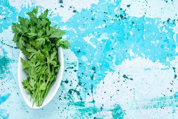 Vue de dessus des verts frais isolés à l'intérieur de la plaque sur le sol bleu vif produit feuille verte repas alimentaire