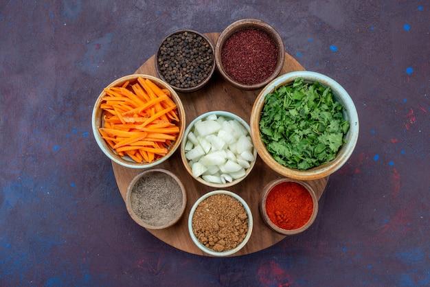Vue de dessus les verts et les légumes avec des assaisonnements sur la surface sombre des aliments végétaux poivre