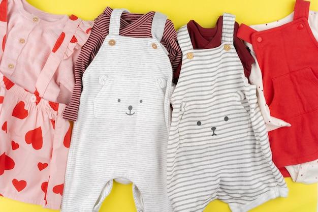 Vue de dessus des vêtements de bébé fille sur jaune