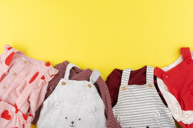 Vue de dessus des vêtements de bébé fille sur une surface jaune