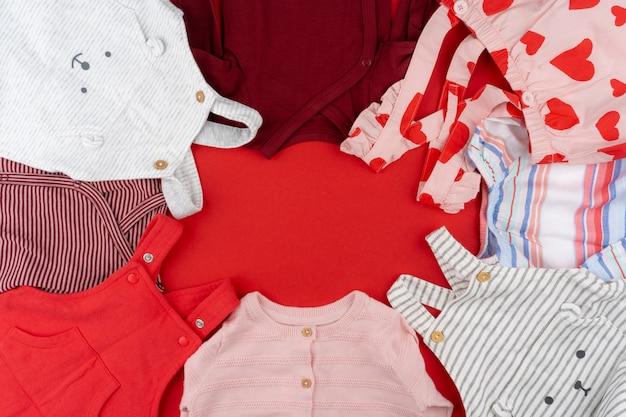 Vue de dessus de vêtements bébé sur fond rouge