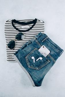 Vue de dessus des vêtements pour femmes t-shirt à rayures, short en denim et accessoires: écouteurs, smartphone.