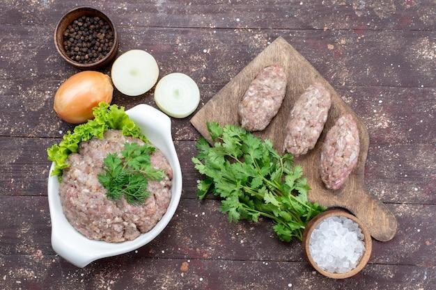 Vue de dessus de la viande crue hachée à l'intérieur de la plaque avec des oignons verts sel sur le bureau brun viande crue repas vert