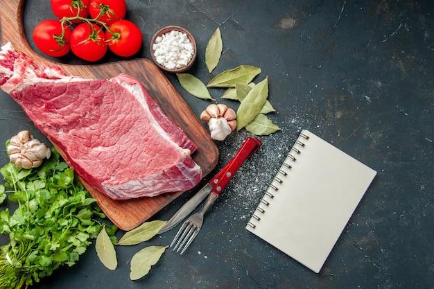 Vue de dessus de la viande crue tranchée avec des tomates fraîches et des légumes verts. couleur nourriture viande cuisson repas