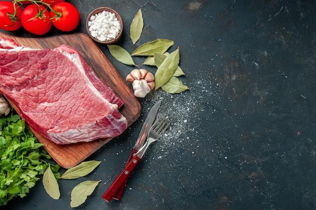 Vue de dessus de la viande crue tranchée avec des tomates rouges et des verts. nourriture viande cuisine repas