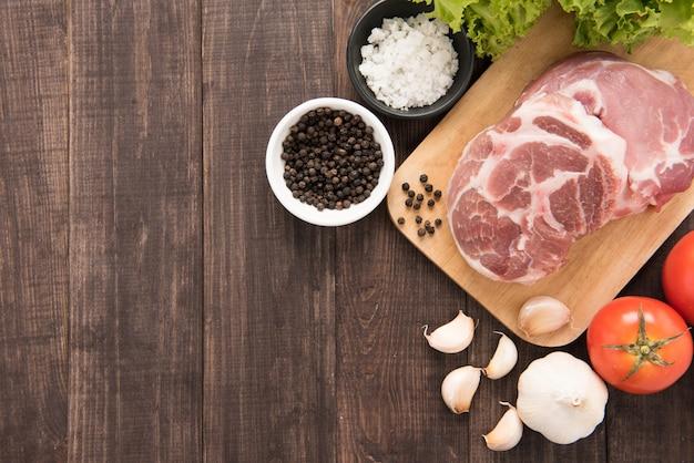 Vue de dessus de la viande fraîche crue et des légumes sur fond de bois