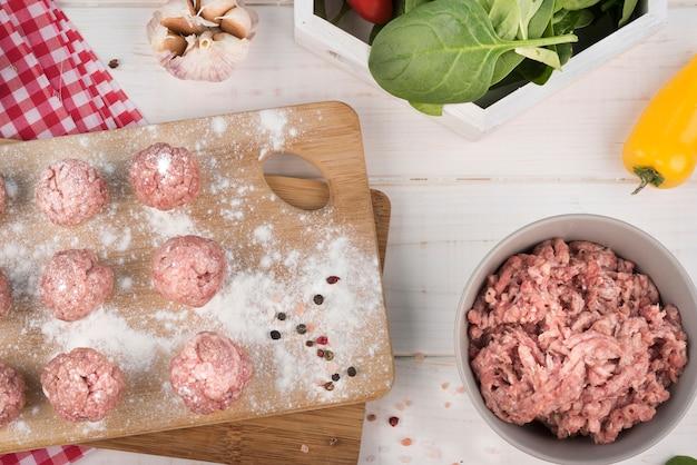 Vue de dessus de viande hachée et boulettes de viande sur planche de bois