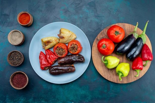 Vue de dessus de la viande à l'intérieur des légumes dolma à l'intérieur de la plaque avec des légumes frais sur le bureau bleu foncé nourriture viande dîner d'engraissement santé