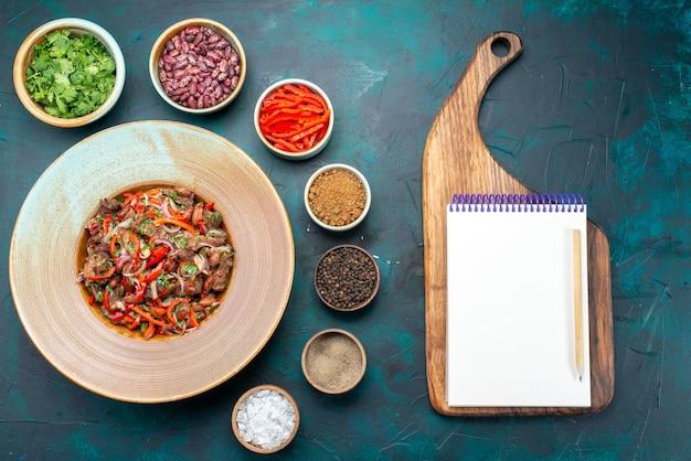 Vue de dessus de la viande avec des légumes tranchés avec des haricots verts ainsi que des assaisonnements bloc-notes sur la viande de repas de fond bleu foncé