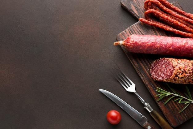 Vue de dessus de la viande de porc avec des saucisses sur la table