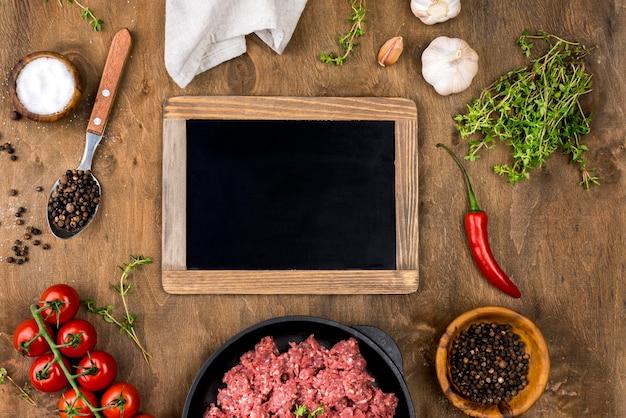 Vue de dessus de la viande avec tableau noir et tomates