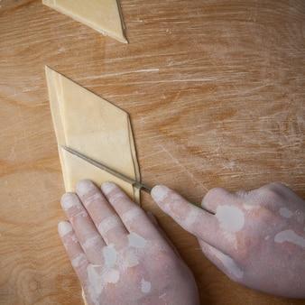 Vue de dessus xengel avec de la pâte avec un losange et des mains humaines et un couteau