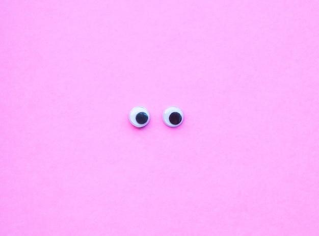 Vue de dessus des yeux écarquillés sur fond rose avec espace copie.