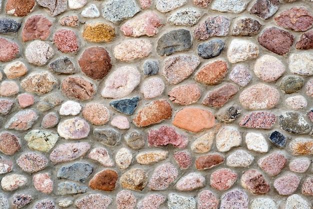 Vue de détail plat d'un mur fait de différentes pierres. abstrait de pierre.