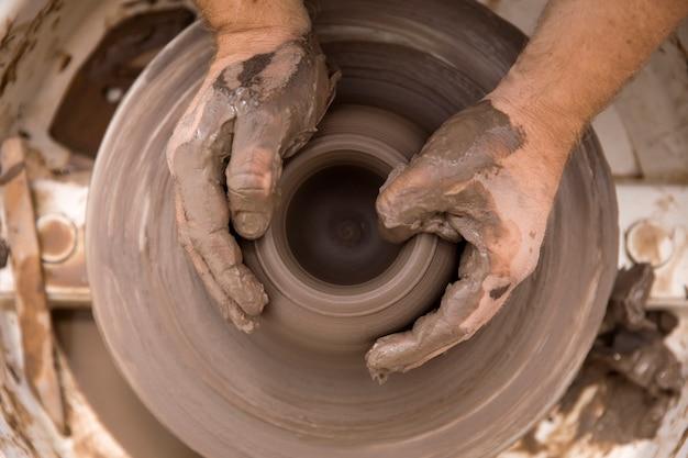 Une vue détaillée d'un artiste fait de la poterie d'argile sur une roue rotative