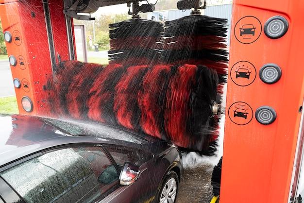 Vue détaillée sur le lavage de voiture, l'eau de mousse de lavage de voiture, le lavage de voiture automatique en action