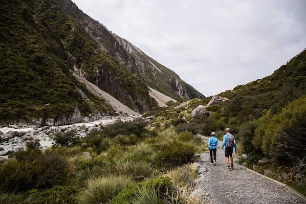 Vue de deux personnes en randonnée dans les falaises couvertes d'arbres avec une rivière entre les falaises