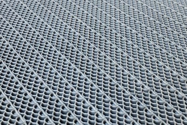 Vue diagonale de la surface perforée en caoutchouc, en métal ou en plastique avec un motif détaillé.