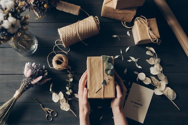 Vue directement au-dessus de la femme d'emballage des cadeaux en papier kraft à l'aide de brindille pour la décoration en magasin