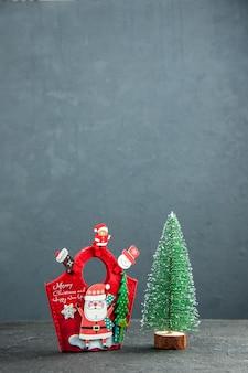 Vue à distance de l'ambiance de noël avec des accessoires de décoration sur une boîte cadeau du nouvel an et un arbre de noël sur une surface sombre