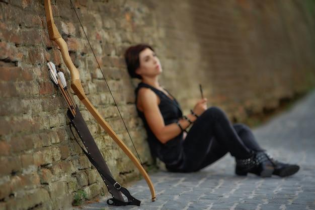 Vue de la distance de la femme au repos après le tir de l'arc.