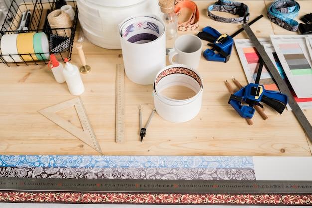 Vue de divers outils à main, fournitures pour faire des colliers, des papiers roulés et des échantillons de textile sur table en bois