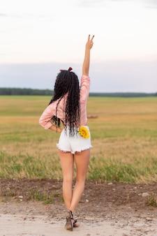 Vue sur le dos d'une femme avec un tournesol dans sa poche de short montrant le signe de la victoire
