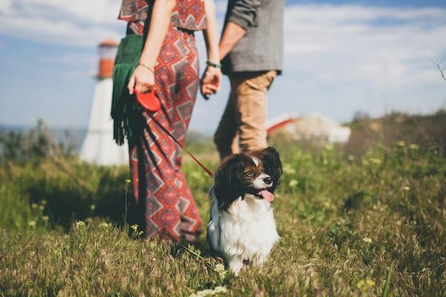 Vue de dos sur le jeune couple hipster élégant amoureux marchant avec un chien dans la campagne