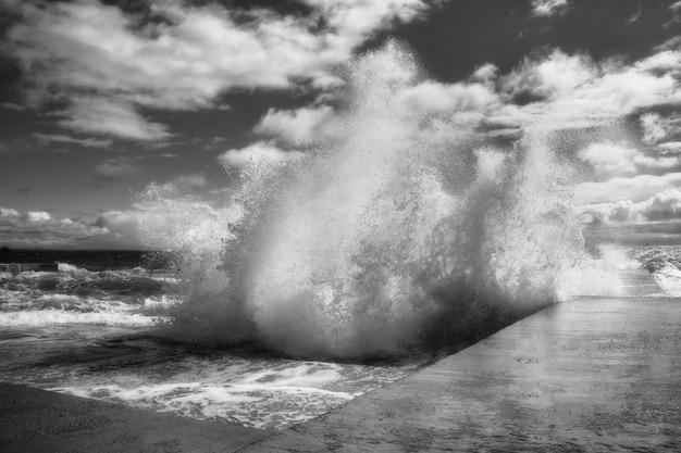 Vue dramatique des vagues de la mer s'écrasant contre la puissance de la jetée en béton de la nature en noir et blanc