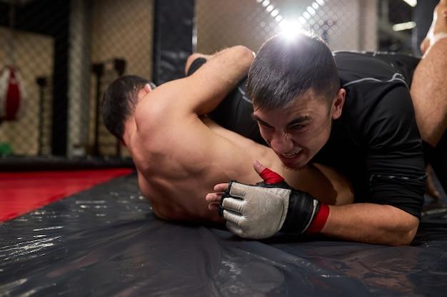 Vue du faible angle de deux combattants professionnels luttant dans une salle de sport. boxeurs forts avec des combats de corps parfaits, essayez de gagner le combat, hommes forts agressifs engagés dans le sport mma