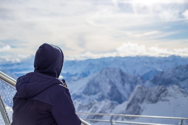 Vue du gars de l'arrière qui regarde les hautes montagnes alpines