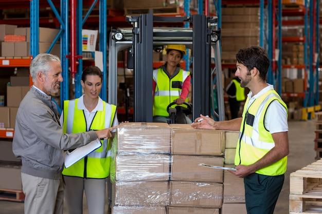 Vue du gestionnaire parle avec le travailleur des marchandises