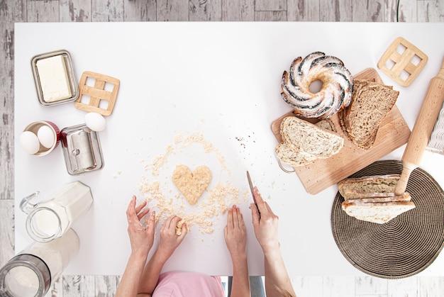 La vue du haut. maman et sa fille préparent des pâtisseries dans la cuisine.