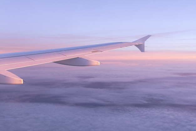 Vue du hublot de l'avion sur le ciel de couleur rose avec des nuages d'air et l'aile de l'avion