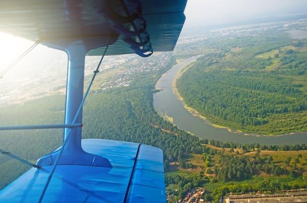 Une vue du hublot d'un biplan à turbopropulseurs sur la rivière.