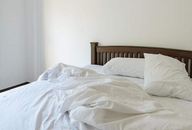 Vue du matin d'un lit blanc défait