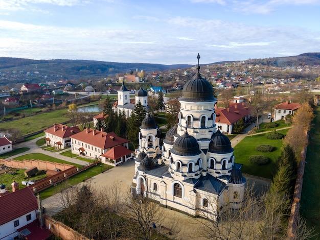 Vue du monastère de capriana depuis le drone. eglises avec champ vert et village. collines au loin. moldavie
